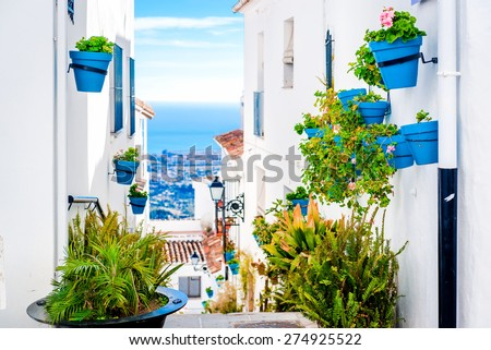 Picturesque street of Mijas with flower pots in facades. Andalusian white village. Costa del Sol. Southern Spain - stock photo
