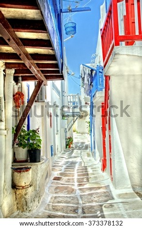 picturesque sunny and colorful cobble stone street at the island of Mykonos, Greece - stock photo