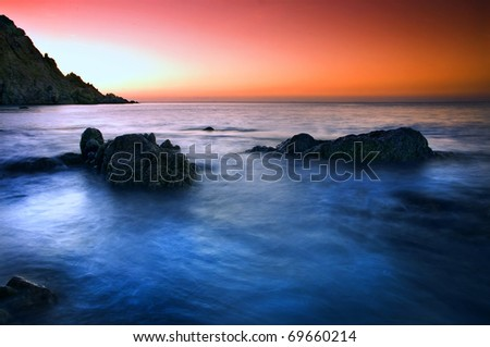 Picturesque sunset and cloudscape over rocky coastline, Socotra or Soqotra island in Indian ocean. - stock photo