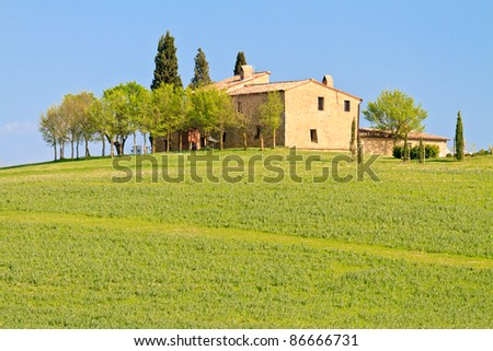 Picturesque tuscan farm house before blue sky, Italy - stock photo