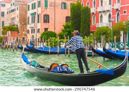 Picturesque view of Gondolas on Canal Grande in hat with blue ribbon and typical striped singlet, Venice, Italy. Selective focus on Gondolier - stock photo