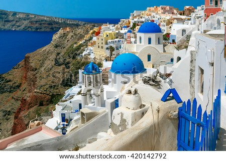Picturesque view of white houses and church with blue domes in Oia or Ia, island Santorini, Greece - stock photo