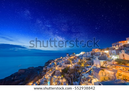 Picturesque view, Old Town of Oia or Ia on the island Santorini, white houses, windmills and church with blue domes with the milkyway Greece