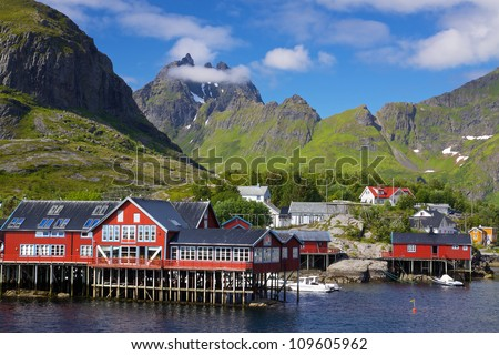Picturesque village on Lofoten islands in Norway surrounded by high peaks of mountains - stock photo
