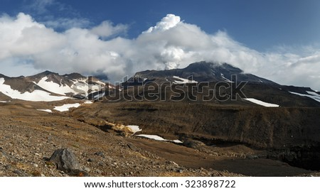 Picturesque volcanic landscape of Kamchatka: beautiful panoramic view of Mutnovsky Volcano, fumarolic activity of volcano - steam and gas emissions from crater. Russia, Far East, Kamchatka Peninsula. - stock photo
