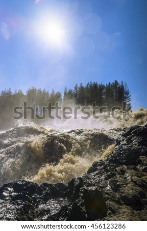 Picturesque waterfall in sunny day, vertical
