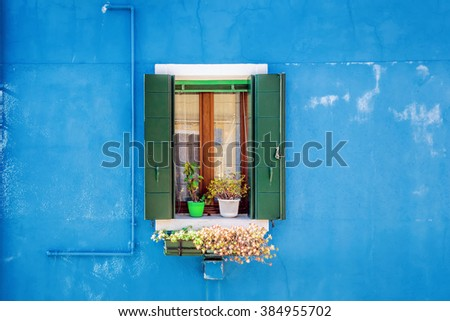 Picturesque window on blue wall of houses on the famous island Burano, Venice, Italy - stock photo