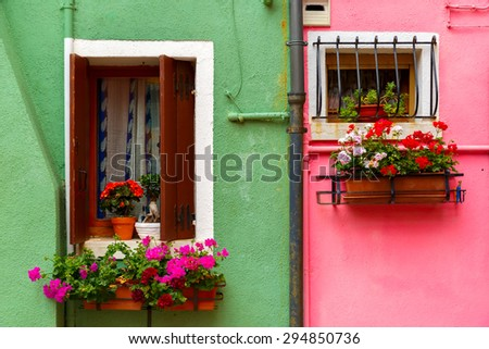 Picturesque windows with shutters and flowers on pink and green wall of houses on the famous island Burano, Venice, Italy - stock photo