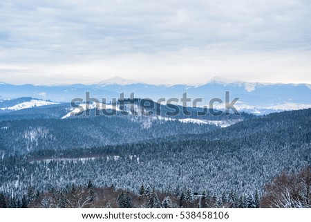 Picturesque winter landscape view in Carpathian mountains with layers of snow, trees, mountain peaks and sky. After the storm a strong frost frosted pine forests between Yaremche Vorokhta Bukovel.