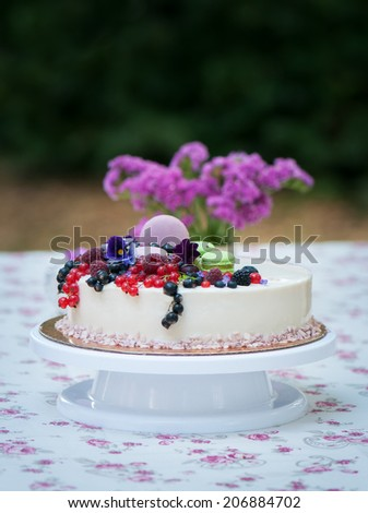 Pie decorated with fresh berries against a flowers and macarons - stock photo
