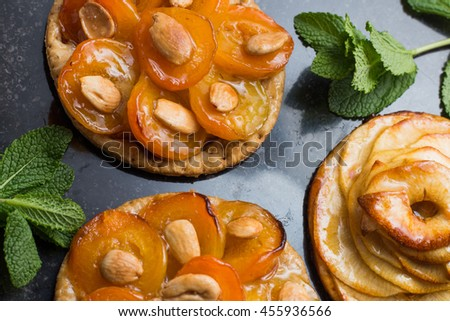 Pie with apricot. Traditional french tart with fruits on dark marble background. Decorated almonds and mint leafs. Delicious dessert with copy space closeup.