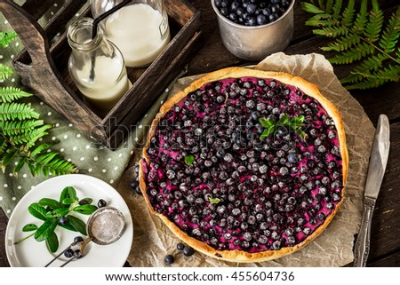 Pie with bilberry and bottle of milk on dark wooden table.Style rustic. Selective focus. - stock photo