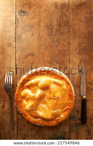 Pie with fork and knife on an old kitchen table. Plenty of copy space. - stock photo