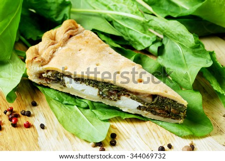 Pie with spinach and feta cheese on a wooden table with spices and fresh spinach - stock photo