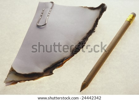 Piece of a burnt paper and the pencil isolated on a white background - stock photo