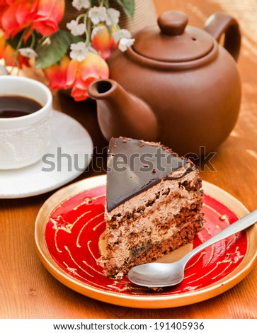 Piece of a chocolate pie on a plate and flowers on a background. Soft focus.