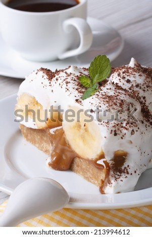 Piece of banana cake with cream and coffee close-up on the table. vertical  - stock photo