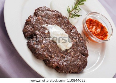 Piece of beef is served on a plate with chilly sauce. - stock photo