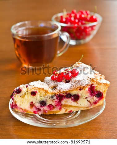 Piece of berry pie on saucer and red currants in bowl