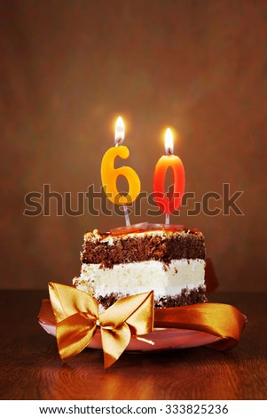 Piece of Birthday Chocolate Cake with Burning Candle as a Number Sixty on Brown Background - stock photo