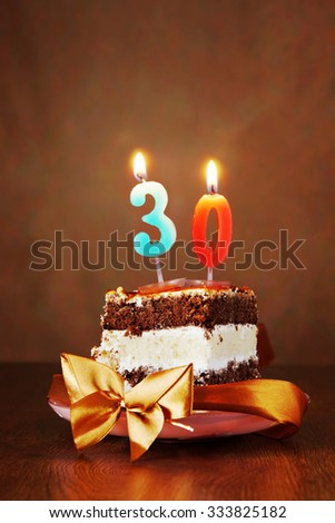 Piece of Birthday Chocolate Cake with Burning Candle as a Number Thirty on Brown Background - stock photo