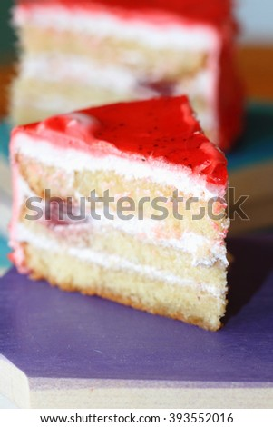 piece of biscuit cake with yogurt cream and strawberry on wooden boards
