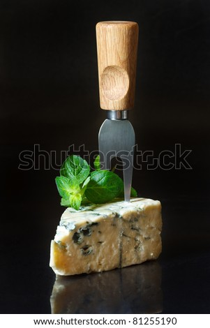 Piece of blue cheese with fork and mint on a black background.