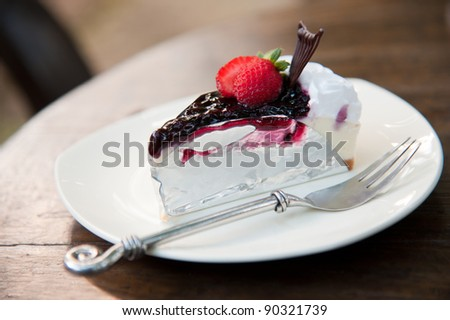 Piece of Blueberry Cheesecake topping with fresh strawberries on white plate closeup - stock photo