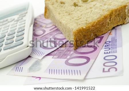 Piece of bread on Euro money. Food budget. - stock photo