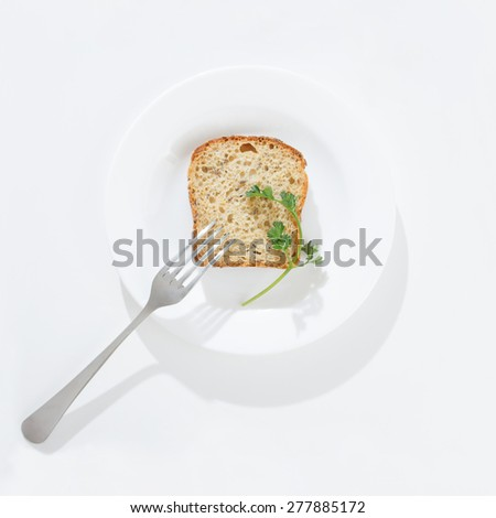 piece of bread with fork on a white bowl - stock photo