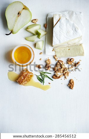 piece of brie, pear? honey and walnuts over white - stock photo