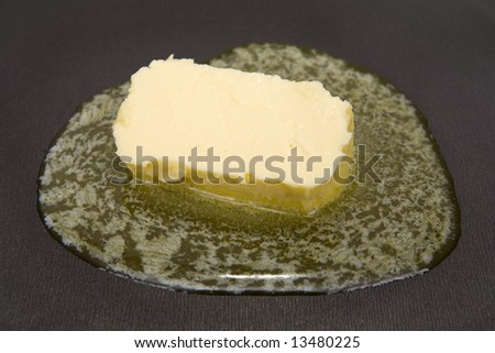 Piece of butter melting on non-stick frying pan - stock photo