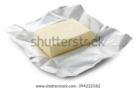 Piece of butter on paper, closeup - stock photo