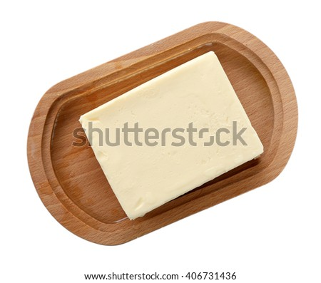 Piece of butter on wooden plate, closeup - stock photo