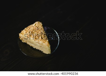 Piece of cake Napoleon, yellow layer cake with glass on a saucer on a dark wood table top - stock photo