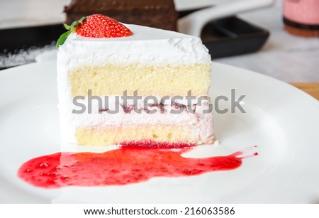 piece of cake on white plate with strawberries sauce