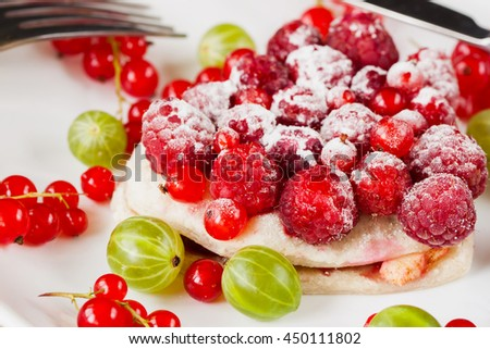 Piece of cake with fresh berries on white plate - stock photo