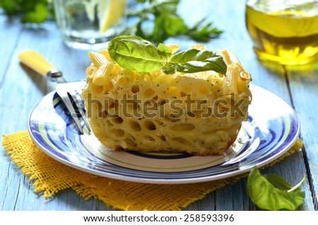 Piece of casserole from penne,eggs and cheese. - stock photo