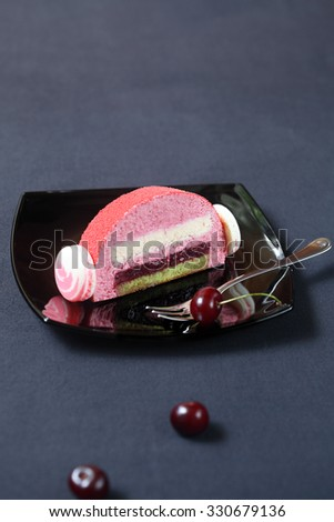 Piece of Cherry Lychee and Pistachio Yule Log Cake, decorated with macaron shells and red velvet spray, on a black square plate and dark background. - stock photo