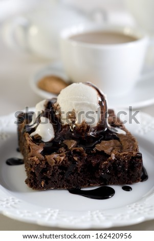 Piece of chocolate brownie with vanilla ice cream and chocolate sauce. - stock photo
