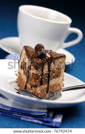 Piece of chocolate cake close-up in white plate and white cup of coffee on blue background.