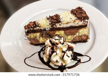 Piece of chocolate cake, decorated, in pastry shop. - stock photo