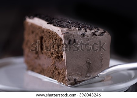 Piece of chocolate cake on a cake lift. View angle from the rear