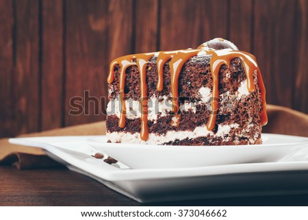 Piece of chocolate cake with caramel on wooden background - stock photo