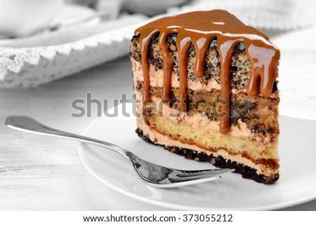 Piece of chocolate cake with caramel on wooden table closeup
