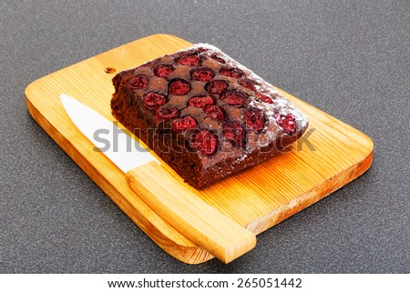 Piece of chocolate cake with cherry and knife - stock photo