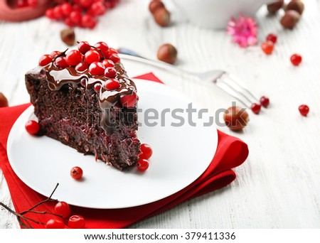 Piece of chocolate cake with cranberries on plate with nuts on wooden table, closeup