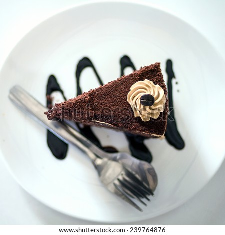 Piece of chocolate cake with icing on white isolated background Coffee cake - stock photo