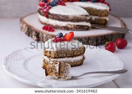 Piece of Earl Grey naked cake with cream cheese and berries and mashed strawberries in brandy inside, on white plate with strawberry, red currant and blueberry, with dessert fork - stock photo