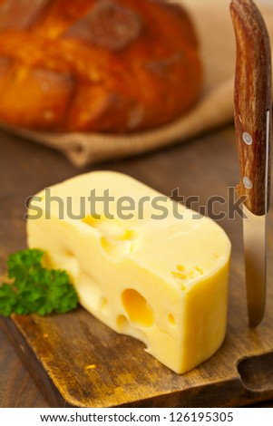 Piece of fresh organic edam cheese on wooden board with fresh bread on breakfast kitchen table